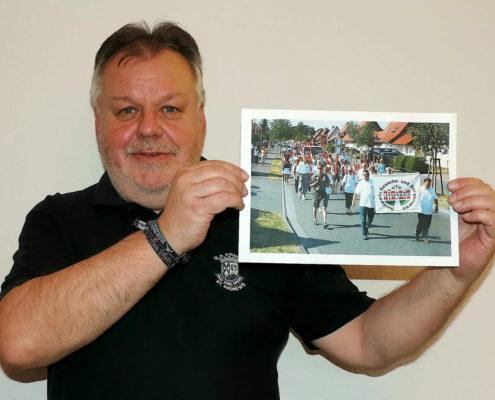 Wolfram Richter mit einem Foto des Festumzuges zum 80-jährigen Ortsjubiläums (Foto: Hajo Eckert)